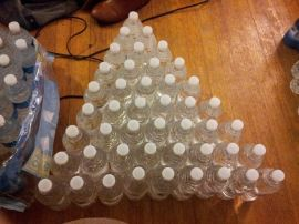 Aerin Johnson organizes her water bottles as she labels them.