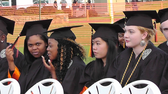 Lacreisha James, Tameisha James, and Aerin Johnson wait to be called to the podium in Webster Groves High School's graduation ceremony on Mary 15, 2015 at Moss Field.